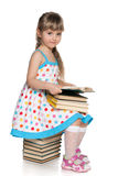Little girl reading on the pile of books Stock Image