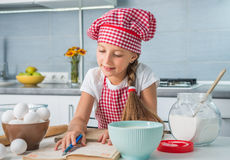 Little girl reading a recipe Royalty Free Stock Images