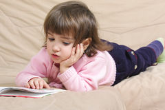 Little girl reading on sofa Royalty Free Stock Photos