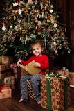 Little girl is reading stories in a book by a Christmas tree. Red shirt of pajamas. Sits on gift boxes. Royalty Free Stock Photography