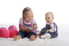 Little girl reading a story for her sister. Little girl reading a story for her baby sister Royalty Free Stock Photos