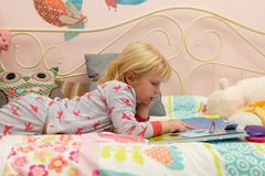 Little Girl Reading a Storybook in Bed Royalty Free Stock Images