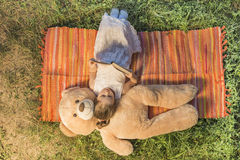 Little girl reading to her plush friend. Beautiful little girl lying down on the picnic blanket with teddy bear toy outside in backyard playground, reading to Stock Images