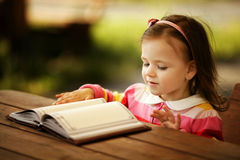 Little girl reads book Royalty Free Stock Images