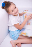 Little girl reads a book. Cute little girl is reading book while sitting on a couch, indoor shoot Stock Photos