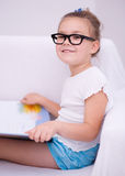 Little girl reads a book. Cute little girl is reading book while sitting on a couch, indoor shoot Stock Photo