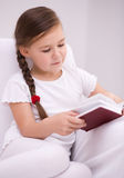 Little girl reads a book Stock Photos