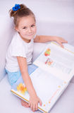 Little girl reads a book Stock Image