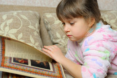 The little girl reads the book lying on a sofa Stock Image