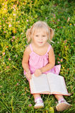 Little girl reads book. Royalty Free Stock Images