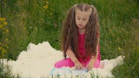 Girl reads a book sitting on the lawn. Little girl reads a book sitting on the lawn stock video footage