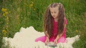 Girl reads a book sitting on the lawn. Little girl reads a book sitting on the lawn stock video