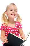 Little girl reads book and smiles. Young blonde child is smiling while reading a book isolated on white stock photos