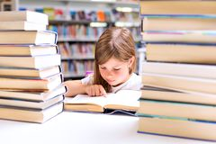 Little girl reads a book surrounded with piles of books in libra stock photography