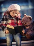 Little girl reads the book Stock Images