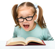 Little girl reads a book while wearing glasses Stock Photo