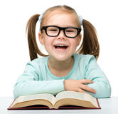 Little girl reads a book while wearing glasses Royalty Free Stock Photo