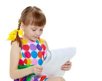 A little girl reads the booklet. stock photography
