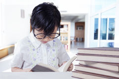 Little girl reads books on desk at home Stock Image