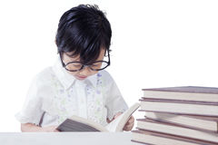 Little girl reads books on table Stock Photos