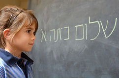 Little girl reads Hello First Grade greetings in Hebrew. Little girl (Age 5-6) reads Hello First Grade greetings in Hebrew (Shalom Kita Alef) on a chalkboard in stock photo