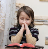 Holy Bible. The little girl reads the Holy Bible Royalty Free Stock Photo