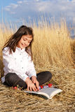 Little girl reads on the meadow. Little cute girl reads on the meadow stock images