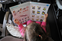 Little girl reads the safety information card Royalty Free Stock Image