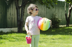 Little girl ready for beach. Carry ball and toys Royalty Free Stock Photos