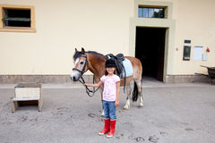 Little girl ready for a horseback riding lesson Stock Images