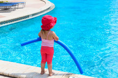 Little girl ready to jump into the pool with noodle Stock Photos