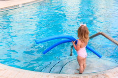 Little girl ready to jump into the pool with noodle Royalty Free Stock Images