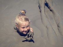 A little girl receives medical treatments in a mud volcano. Treatment of diseases using alternative medicine Royalty Free Stock Image