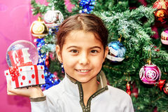 Little girl  receiving snow globe with love for Christmas repres Stock Photos