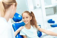 A little girl at a reception with a dentist. She sits in the dental chair and communicates with the dentist Stock Photography