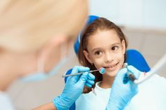 A little girl at a reception with a dentist. Female doctor preparing to examine the teeth of a girl. Girl smiling Stock Photos
