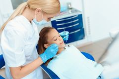 A little girl at a reception with a dentist. Female doctor preparing to examine the teeth of a girl Royalty Free Stock Photos