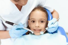A little girl at a reception with a dentist. Female doctor preparing to examine the teeth of a girl Royalty Free Stock Images