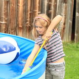 Little girl recharging water gun Royalty Free Stock Photography