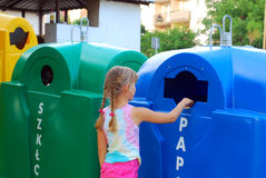 Little girl and recycling. Little girl throws paper waste into special recycling trash bin Stock Photos