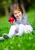 Little girl with red apple sitting on the green grass Royalty Free Stock Photography