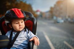 Little girl in the seat bicycle. Little girl in red and black helm in the seat bicycle Royalty Free Stock Photo