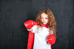 Little girl in red boxing gloves showing aggressive face express Royalty Free Stock Photos