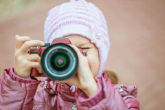 Little girl in with red camera photographs Royalty Free Stock Photo