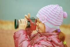 Little girl in with red camera photographs Stock Image
