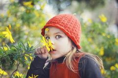Little girl with red cap sniffing flowers. Girl in a red dress Royalty Free Stock Photography