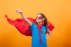 Little girl in red cape plays superhero in studio over yellow background royalty free stock photo