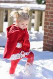 Little girl in red cape walking through fresh snow stock image