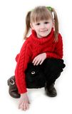 Little girl in red cardigan. Squat down and archly smile Royalty Free Stock Image