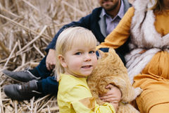 Little girl with red cat among the dry reeds. Stock Photos